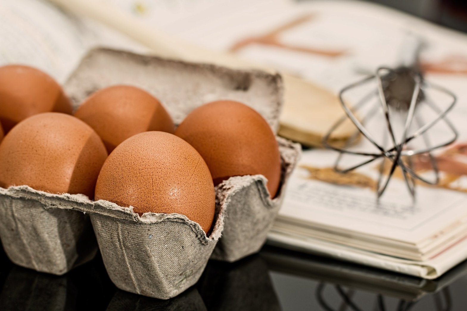 A whisk and eggs on a cookbook